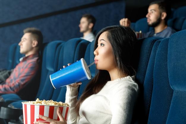 とても楽しかったです。地元の映画館で映画を注意深く見て彼女の飲み物を飲む若いアジア女性の肖像画 Premium写真