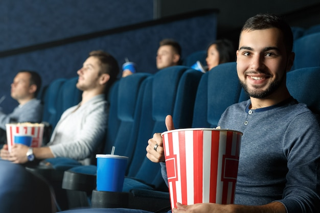 映画マニア。彼のポップコーンを保持している映画館に座って親指を示す若いハンサムなひげを生やした男 Premium写真