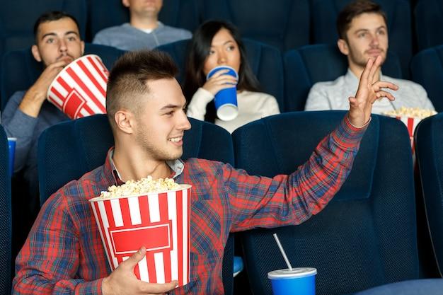 こっち映画を楽しんでいる映画館に座っている間、友人に手を振ってカジュアルな若者 Premium写真
