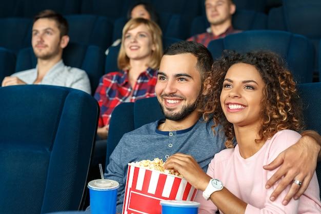 映画のデートナイト!ポップコーンを食べて、映画館で一緒に映画を見て幸せな多文化カップル Premium写真