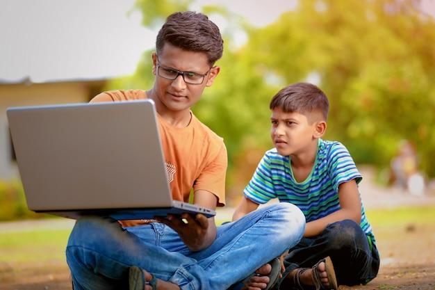 Два индийских брата работают на ноутбуке Premium Фотографии