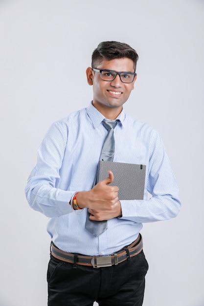 若いインドビジネス男ノートを保持していると強打を示す Premium写真