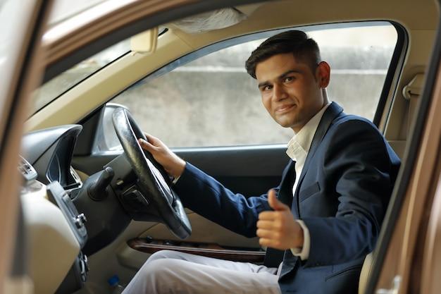 車の窓から強打を示す若いインド人 Premium写真