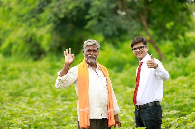 インドの農夫と農学者がグリーンコットンフィールドで強打を見せています Premium写真