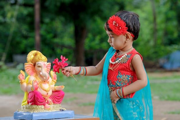Маленькая индийская девочка с лордом ганешей и молиться Premium Фотографии
