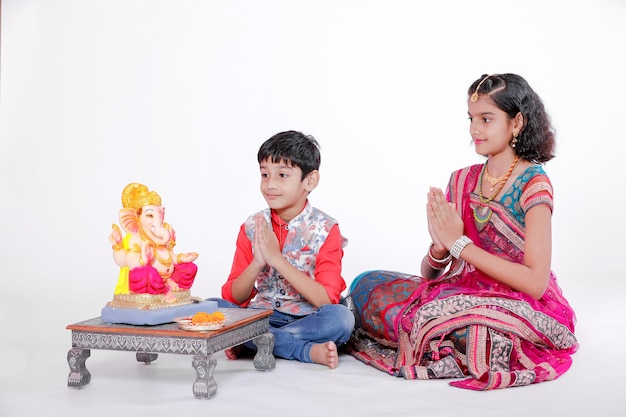 Маленькие индийские дети с лордом ганешей и молитвой, индийский фестиваль ганеша Premium Фотографии