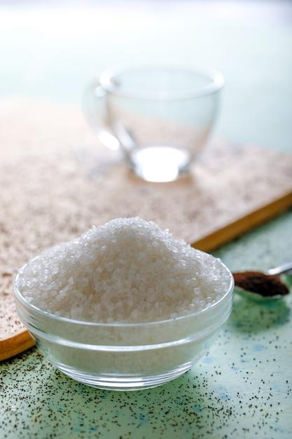木製の背景にガラスのボウルに砂糖 Premium写真
