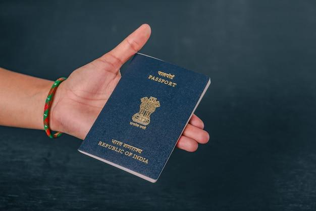 Индийский паспорт в руке, показывая паспорт Premium Фотографии