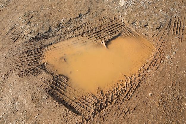水とタイヤホイールと地面にハート型の穴。 Premium写真