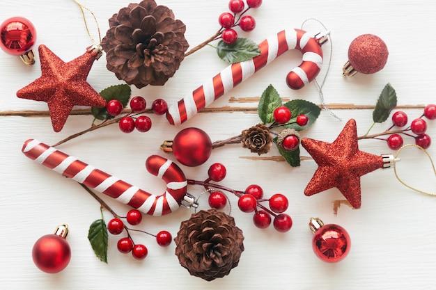 松ぼっくりや針葉樹の円錐形、赤いヒイラギのボール、キラキラ星、キャンディケイン、クリスマスコンセプトで安物の宝石と白い木。クリスマスの壁紙のトップビューフラットレイアウトコピースペースで甘い板背景。 Premium写真