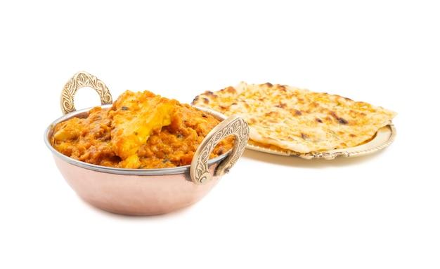 インド料理甘くてスパイシーなパニールパサンダホワイトバックグラウンドにガーリックナン添え Premium写真