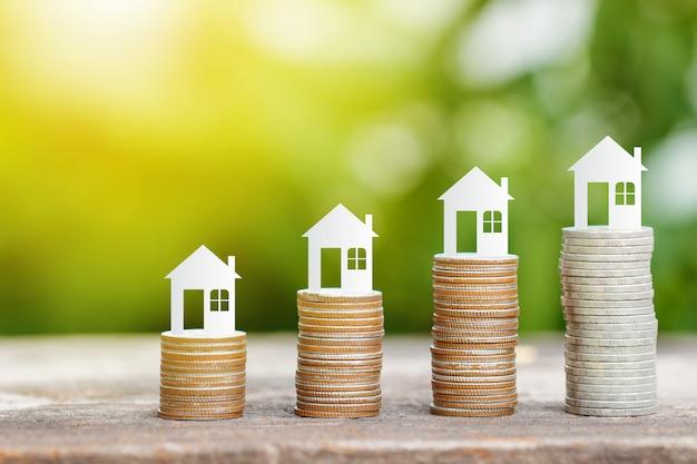 家を買うために保存するためのコインスタック上の家の紙 Premium写真