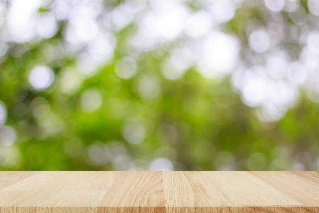 あなたの製品のモンタージュの抽象的なボケ味の明るい背景を持つ空の木製テーブル Premium写真