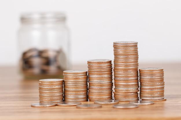 お金の概念を保存するための木製の机の上のコインのスタック Premium写真