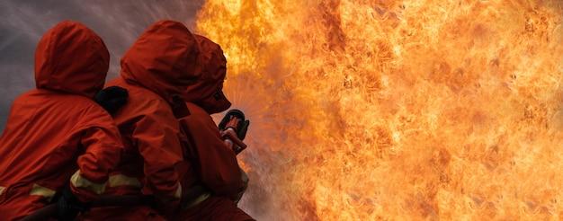 消防士の男は、建物の炎の燃焼を停止します。 Premium写真