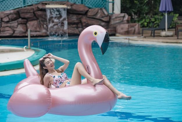 若いアジアの女性は、スイミングプールで巨大なインフレータブルフラミンゴに乗る。 Premium写真