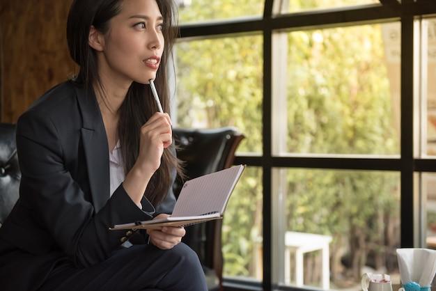 Портрет привлекательной коммерсантки распологая на софу держа тетрадь и заботливый думать о работе. Premium Фотографии