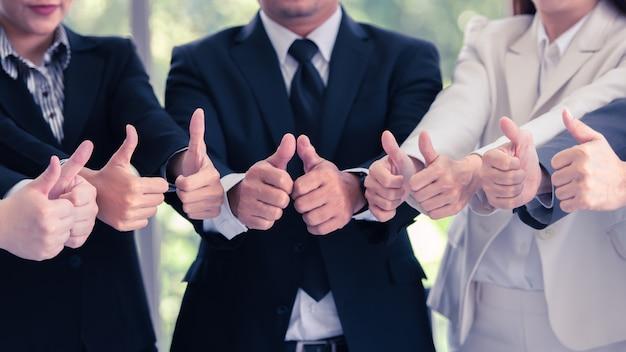 ビジネスマンのチームワークが親指を立て、それを可能にする表現、素晴らしい仕事、戦い続けます。 Premium写真