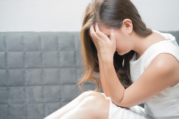 手でソファーに座っていた若い女性は彼女の顔を閉じて悲しい気持ちになりました。 Premium写真