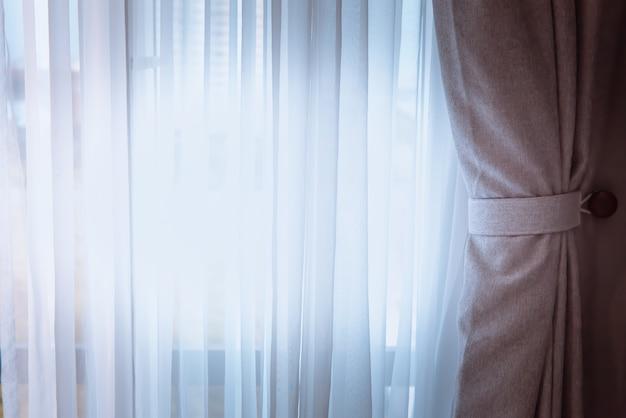 カーテンやカーテンブラインドベッド、室内装飾の概念を持つウィンドウ。 Premium写真