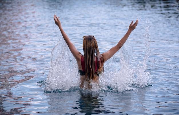 スイミングプールで彼女の頭の中で水しぶきの少女。 Premium写真