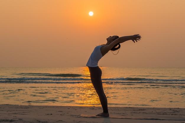 午前中にビーチでヨガのポーズをとる若い健康的なヨガ女性 Premium写真