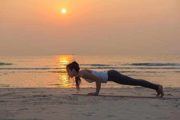 日の出ビーチでヨガのポーズを練習する若い健康的なヨガ女性 Premium写真