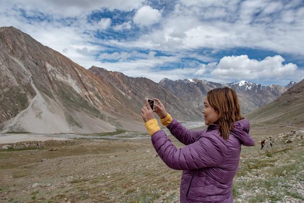 週末に風景の写真を撮りながら携帯電話を持つ観光手 Premium写真