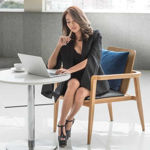 ラップトップに取り組んで椅子に座っている若いオフィスビジネス女性 Premium写真