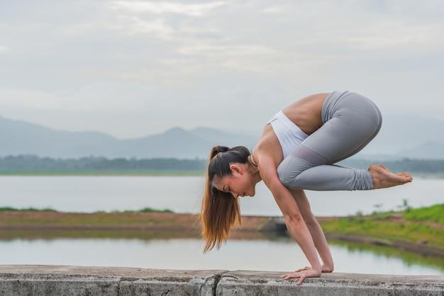 山を背景に湖でヨガをやっている若いスポーツ女性。 Premium写真