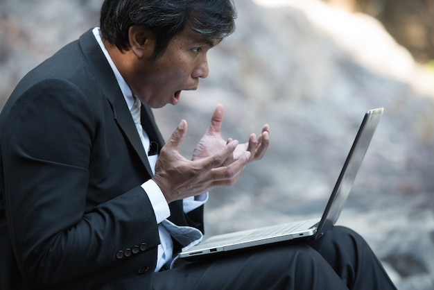 ノートパソコンの画面を見て公園で興奮してスーツを着た驚いた実業家。 Premium写真