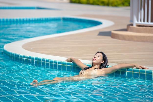アジアの女性がプールでリラックス。 Premium写真