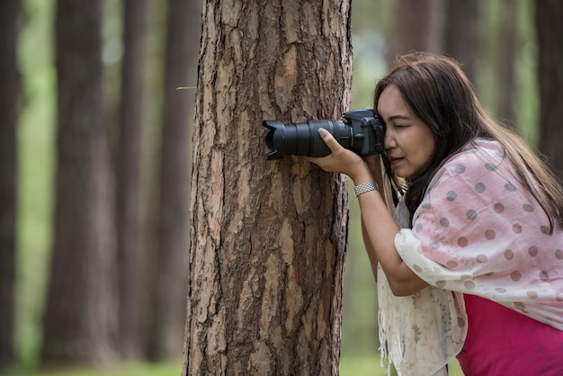 アジアの女性がデジタル一眼レフで写真を撮る、木のコンセプトでポーズを撮影します。 Premium写真