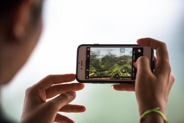 週末に風景の写真を撮りながら携帯電話を持っている観光手、旅行携帯電話のコンセプトで写真を撮る。 Premium写真