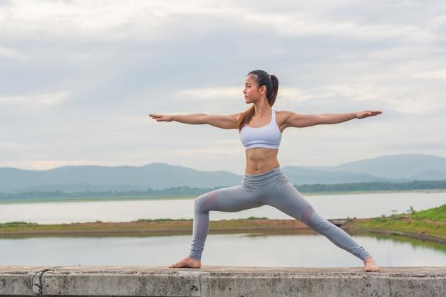 美しい女性は山と湖のほとりにヨガを練習します。 Premium写真