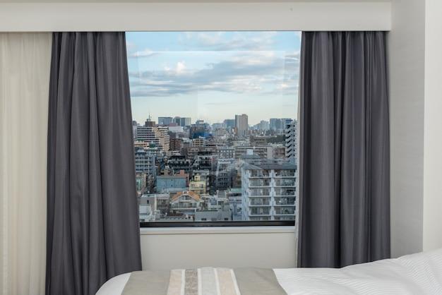 カーテンウィンドウとシティビルトイン付きのベッドルーム Premium写真