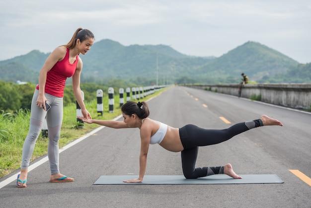 妊娠中の女性が外でヨガをやっているトレーナー。 Premium写真