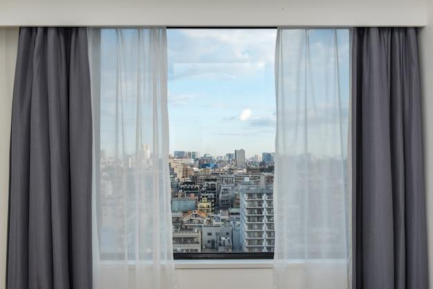 街並みを望むカーテン窓をブラインドします。 Premium写真
