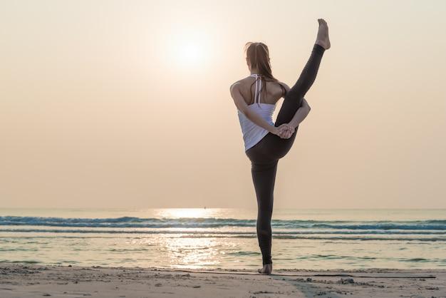 ヨガをやって健康的なヨガ女性は朝のビーチでポーズします。 Premium写真