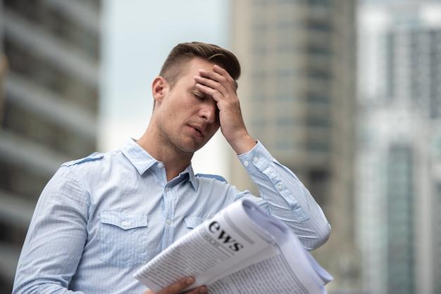 Стресс бизнесмен с газетой беспокоиться о новостях фондового рынка. Premium Фотографии