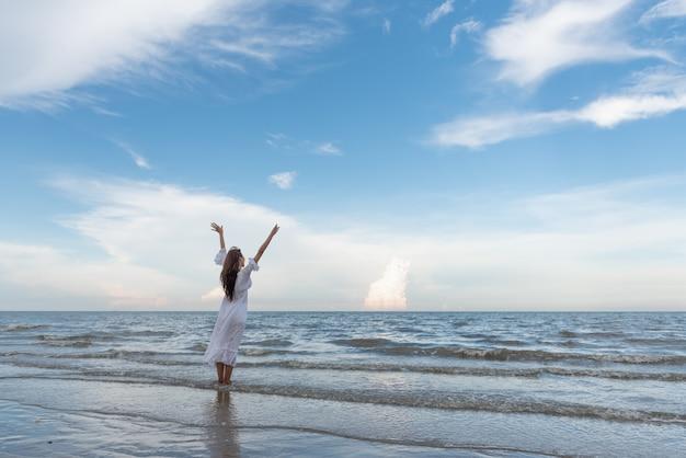 旅行の若いアジアの女性は、ビーチで腕を上げた。 Premium写真