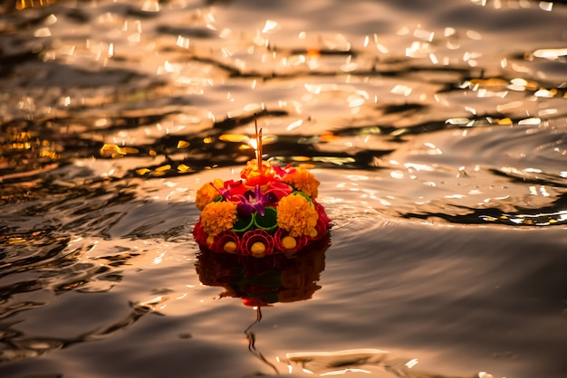Бумажный цветок лотоса со свечой, плавающей на реке ночью в фестивале лой кратонг Premium Фотографии