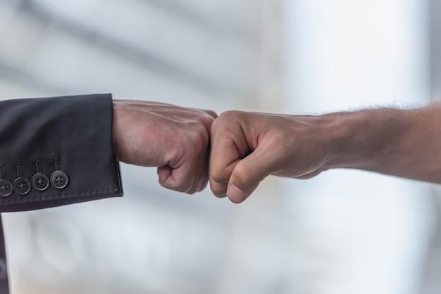拳を与えるビジネス人々は、オフィスでチームワークで一緒にバンプします。 Premium写真