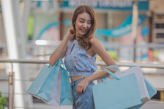 ショッピングコンセプト、モールセンターで買い物袋を保持しているアジアの女性に幸せな時間。 Premium写真