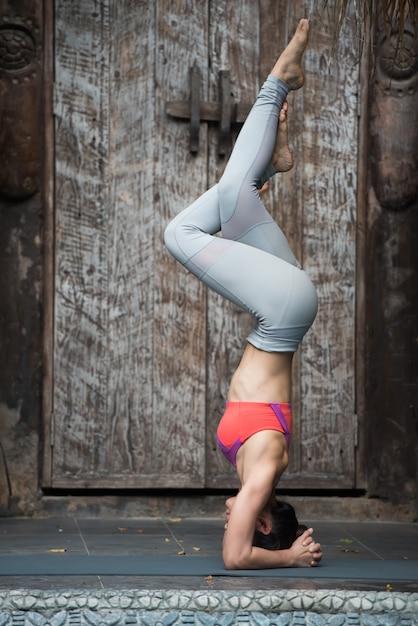 自宅でヨガのポーズでスポーツの若い女性のトレーニング。 Premium写真