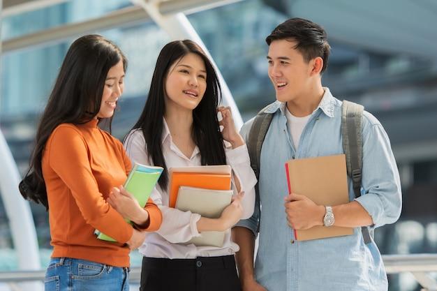キャンパスでの友情、本を持つ大学生は一緒に時間を過ごします。 Premium写真