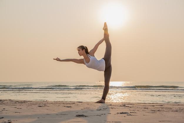 日の出のビーチで若い健康な女性の練習とトレーニングヨガ Premium写真