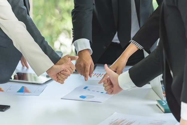 Работа в команде деловых людей указывает на цель на встрече, выражение, вы можете сделать это Premium Фотографии