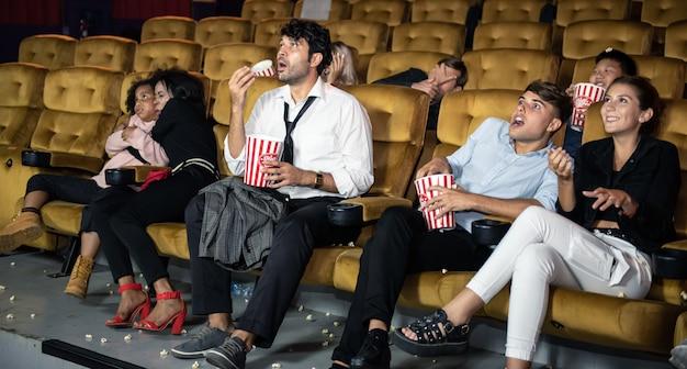 劇場で楽しんで映画を見て幸せな人。 Premium写真