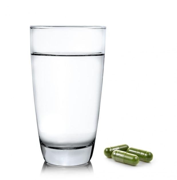 コップ一杯の水とモリンガのカプセル錠剤 Premium写真